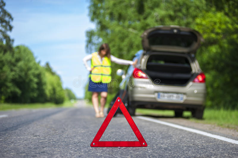 Woman in reflective vest near broken car stock image