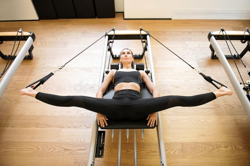 Woman on reformer bed doing hip opening exercises stock photography