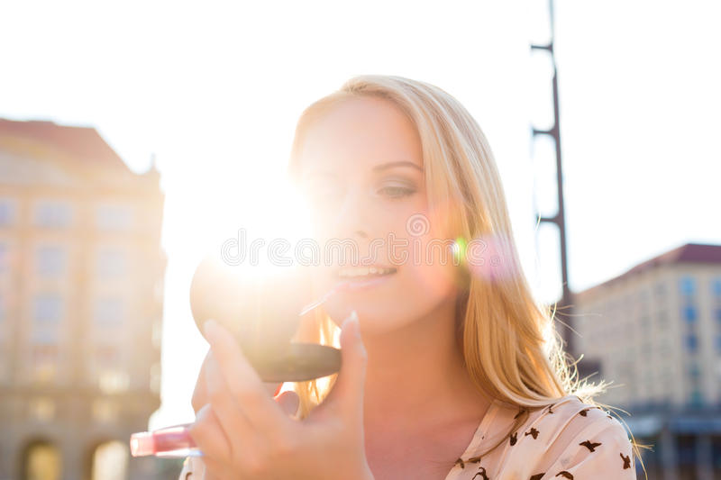 Download Woman Refreshing Makeup With Gloss In The Sun Stock Image - Image: 28156737
