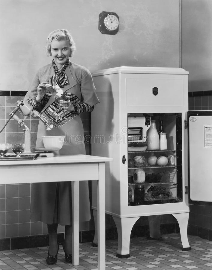 Woman with refrigerator and mixer in kitchen royalty free stock photos