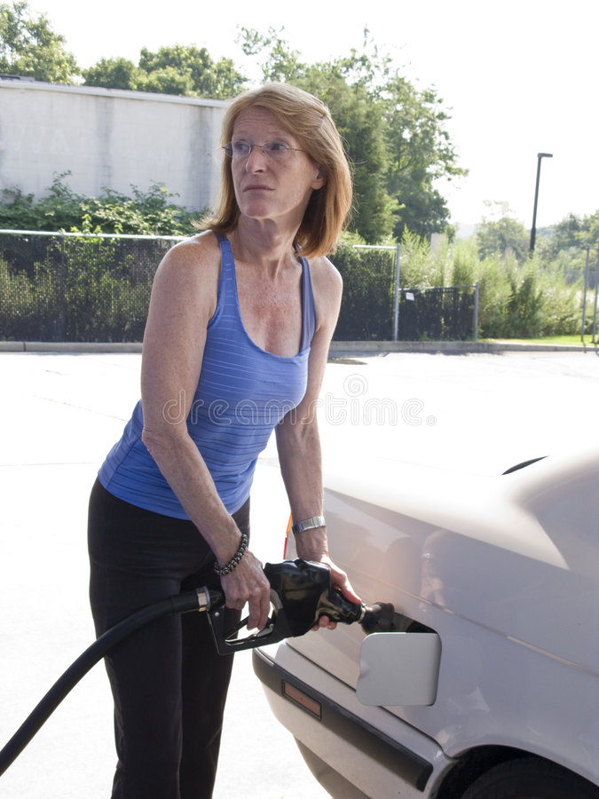 Woman refueling stock image