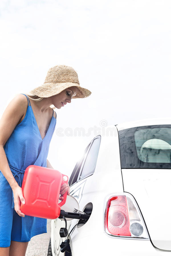 Woman refueling car against clear sky on sunny day stock photo