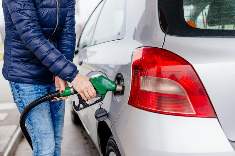 Woman refueling her small silver car stock image