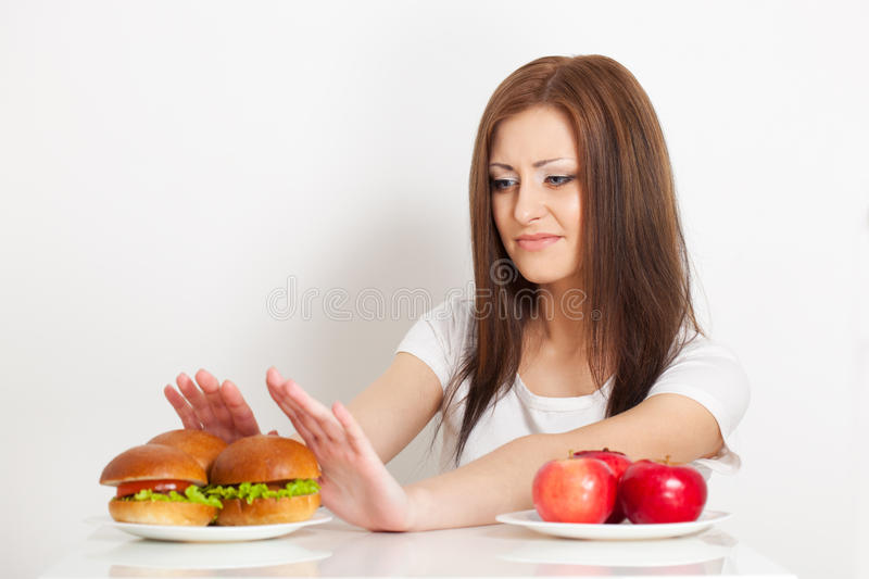 Woman refuses to the junk food. Young beautiful woman refuses to the junk food royalty free stock photography