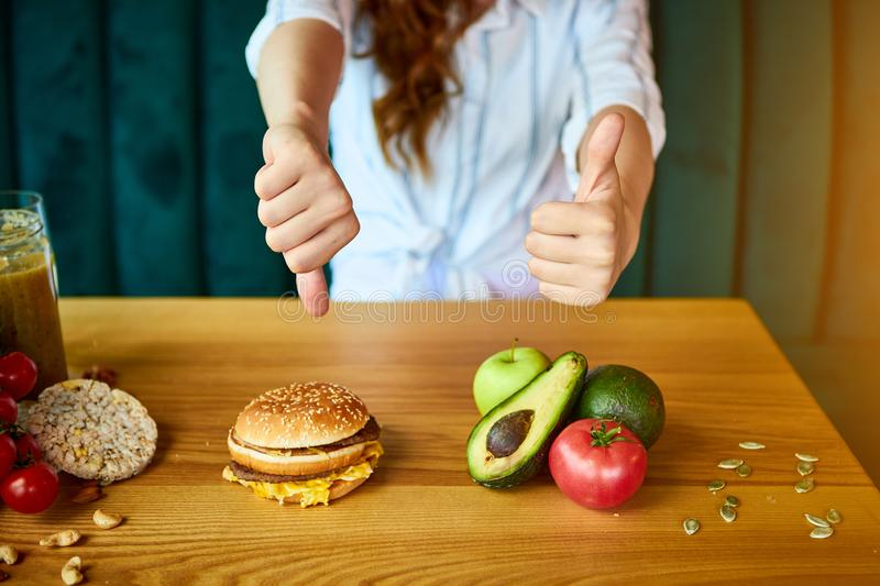 Woman is refusing to eat unhealthy hamburger. Cheap junk food vs healthy diet. Woman is refusing to eat unhealthy hamburger . Cheap junk food vs healthy diet royalty free stock photo