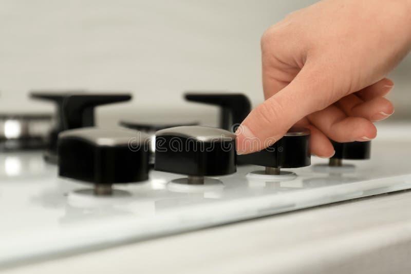 Woman regulating cooking mode on gas stove panel. Closeup royalty free stock photos
