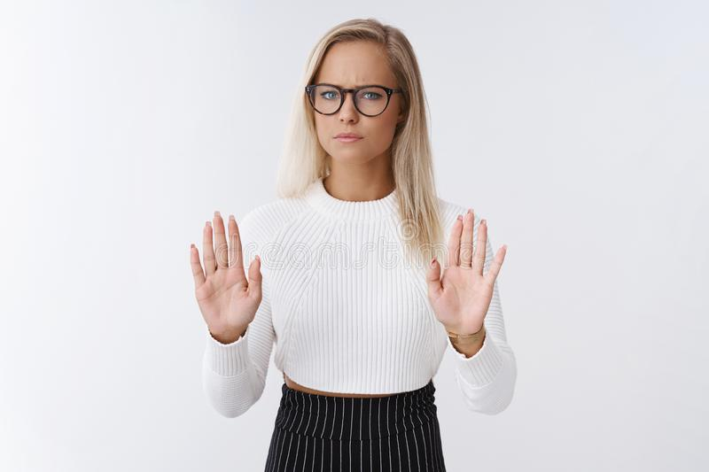 Woman rejects disrespectful offer. Upset and displeased gloomy blond female businesswoman in glasses and cropped sweater. Raising palms in stop and no, refusing stock photos