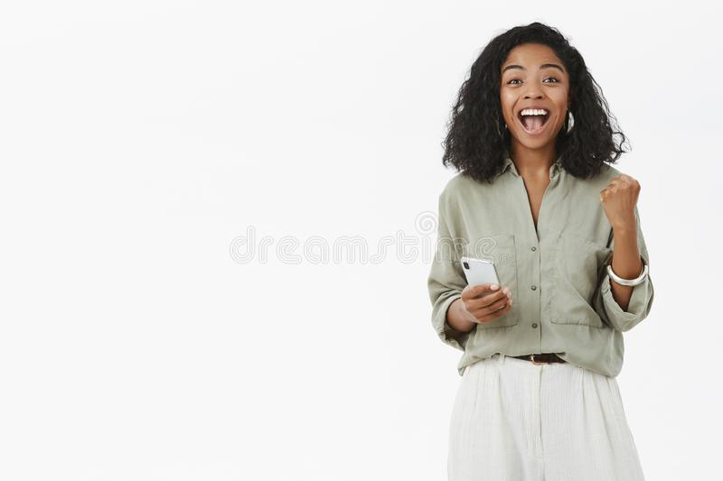 Woman rejoicing screaming from happiness and joy receiving confirmation of enterting university via smartphone clenchign. Fist from delight in success gesture royalty free stock images