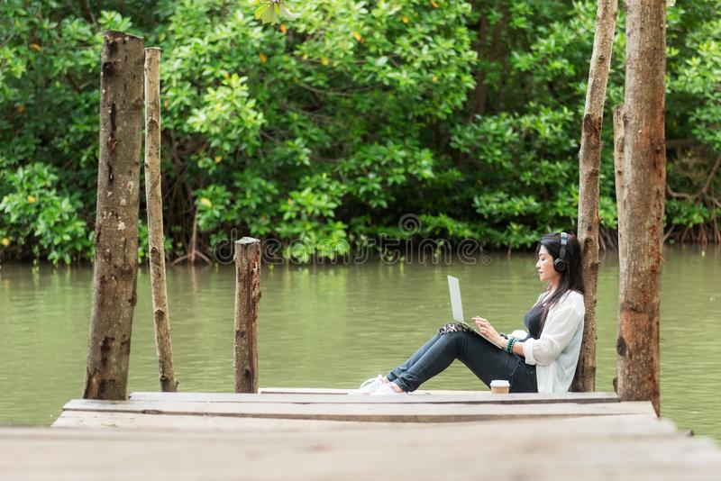 Woman relax and chill while listening music with headphone and laptop in the outdoor education nature green park, girl happy. royalty free stock photos
