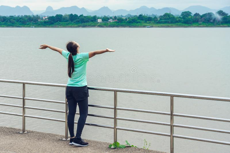 Woman is relax standing after run with a view of the river in the morning. Young woman is relax standing after run with a view of the river in the morning royalty free stock photos