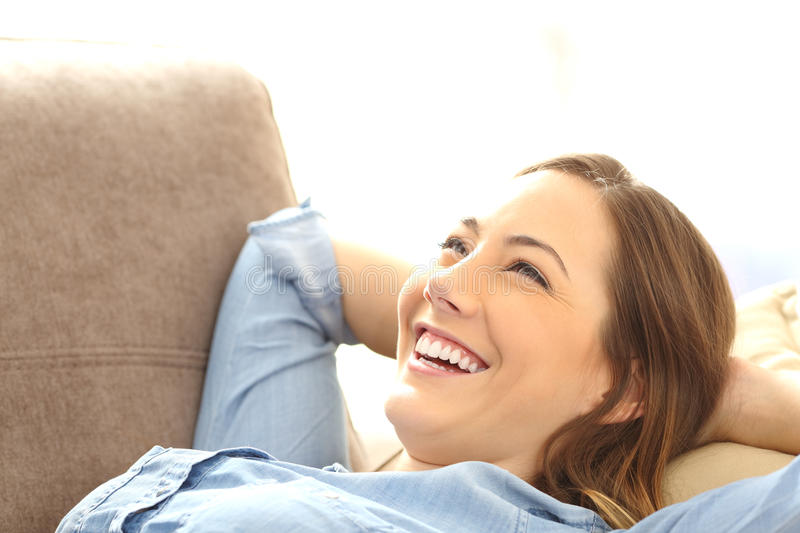 Woman relaxed lying on a couch royalty free stock images