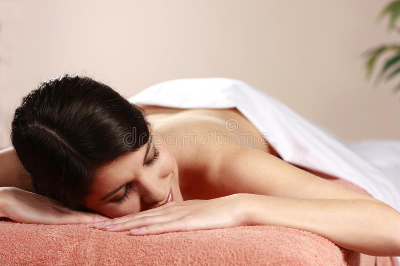 Woman relaxes in day spa. On a massage bench royalty free stock image