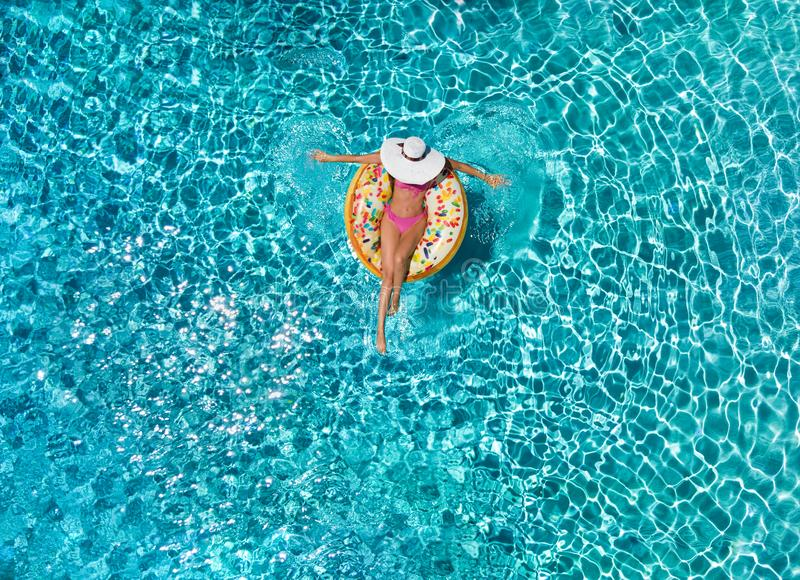 Woman relaxes on a donut shaped float over blue, sparkling pool water. Summer holiday relaxation concept: attractive woman with white hat relaxes on a donut stock photos