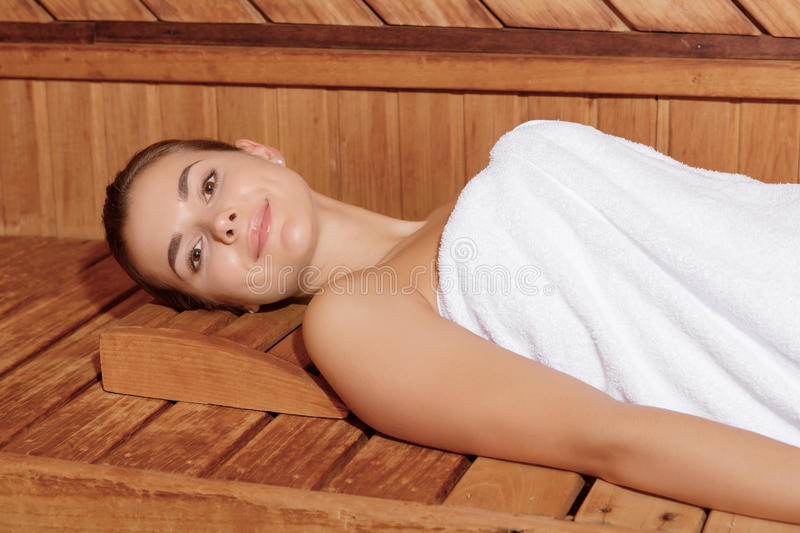 Woman relaxes in sauna stock image