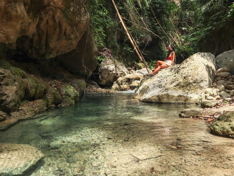 Woman alone on the green canyon in Dao Falls in Cebu Island, Philippines. Woman relaxing alone on the green canyon road at the middle of tropical jungle on the stock image