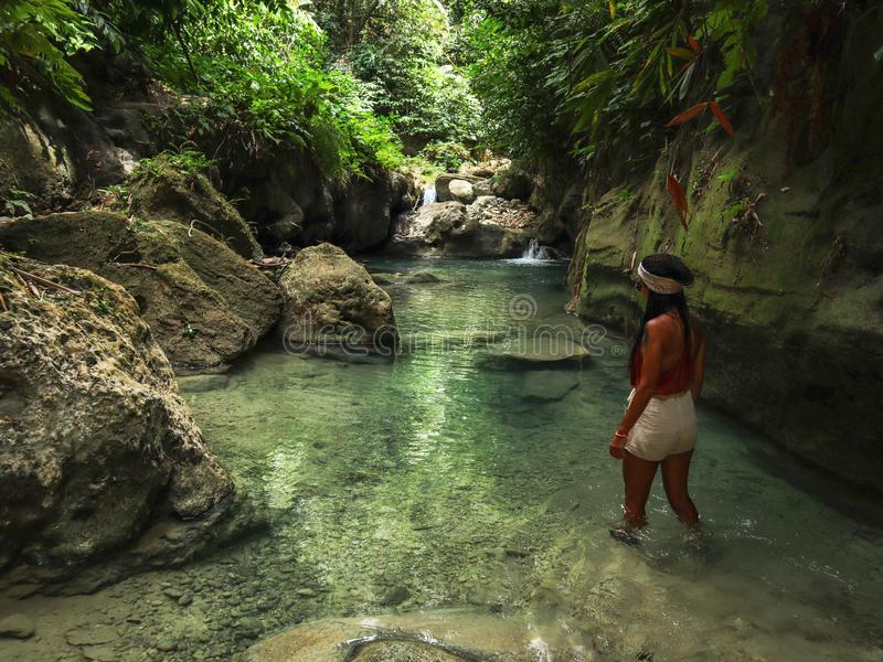 Woman alone on the green canyon in Dao Falls in Cebu Island, Philippines. Woman relaxing alone on the green canyon road at the middle of tropical jungle on the stock images