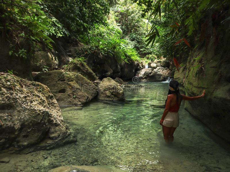 Woman alone on the green canyon in Dao Falls in Cebu Island, Philippines. Woman relaxing alone on the green canyon road at the middle of tropical jungle on the royalty free stock photography