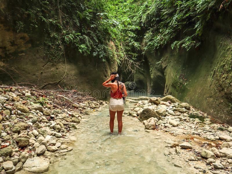 Woman alone on the green canyon in Dao Falls in Cebu Island, Philippines. Woman relaxing alone on the green canyon road at the middle of tropical jungle on the stock photo