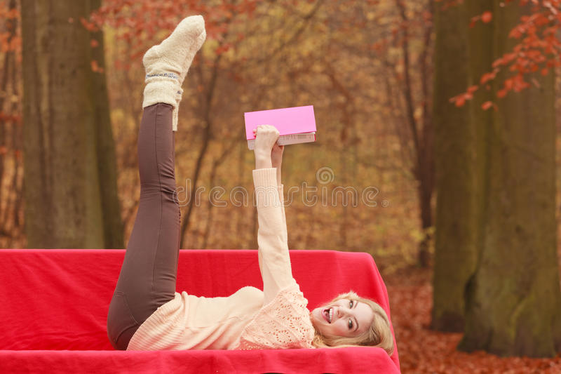 Woman relaxing in autumn fall park reading book. Carefree woman relaxing in fall park reading book. Young blonde girl having fun resting laying on bench. Autumn royalty free stock photo