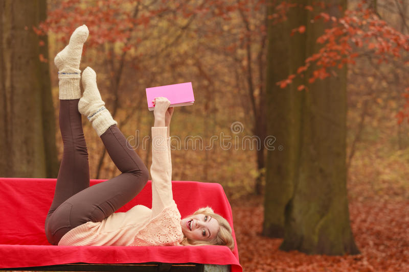 Woman relaxing in autumn fall park reading book. Carefree woman relaxing in fall park reading book. Young blonde girl having fun resting laying on bench. Autumn royalty free stock photos