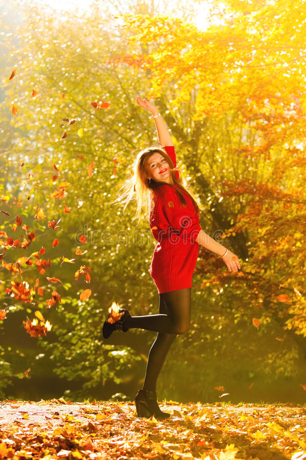Woman Relaxing In Autumn Park Throwing Leaves Up In The ...