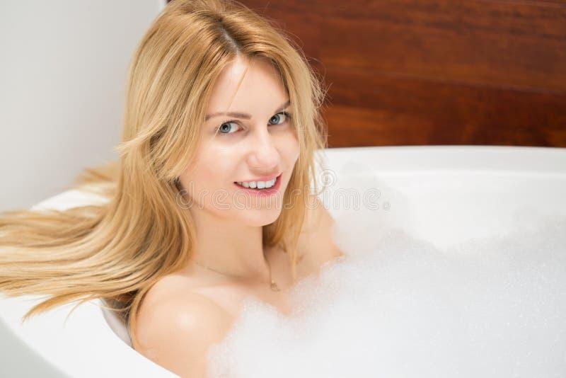 Woman relaxing in the bathtub. Beauty blonde woman relaxing in the bathtub royalty free stock image