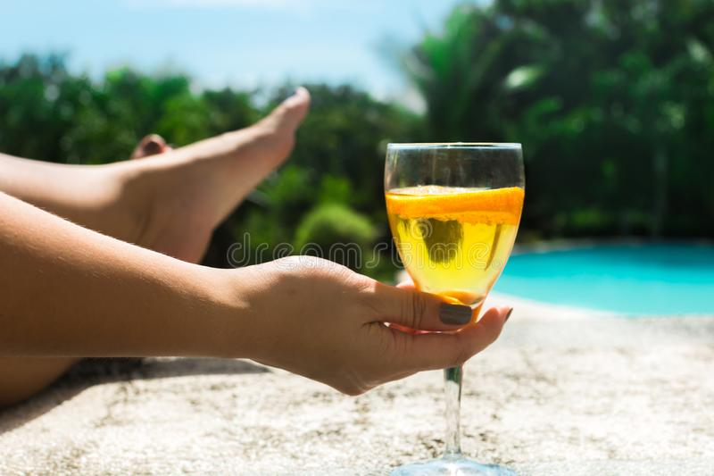 Woman relaxing on beach with a cocktail, at a vacation resort stock images