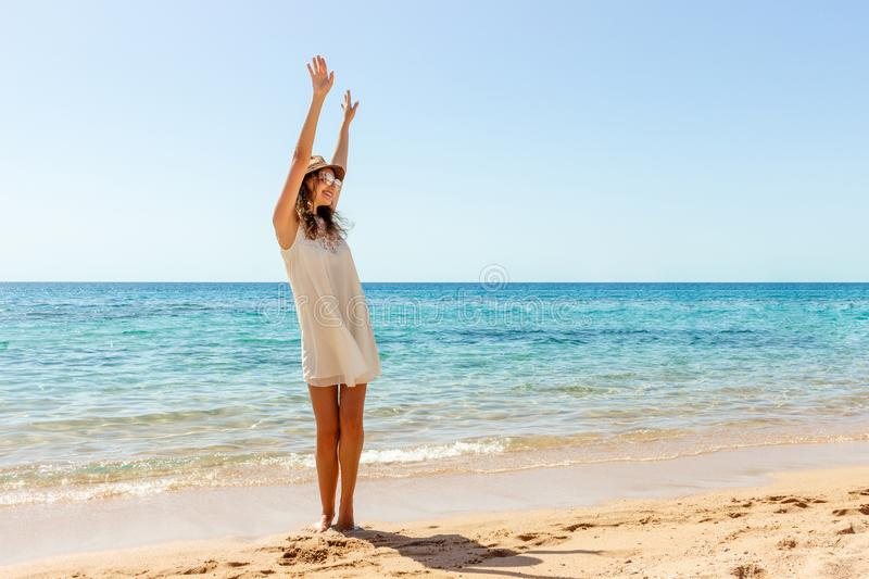 Woman relaxing at beach enjoying summer freedom. Happ girl at the beach royalty free stock images