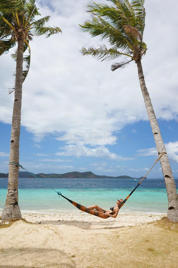 Woman relaxing at the beach on a hammock royalty free stock photos