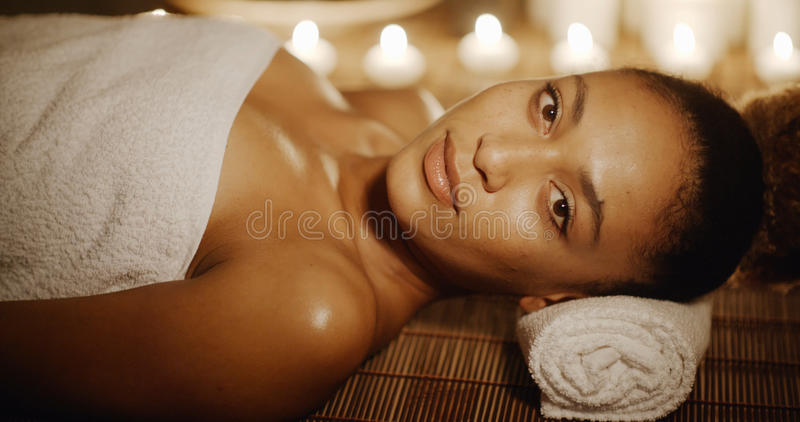 Woman Relaxing At Beauty Spa. Young woman relaxing at beauty spa by candle light and looking at camera royalty free stock image
