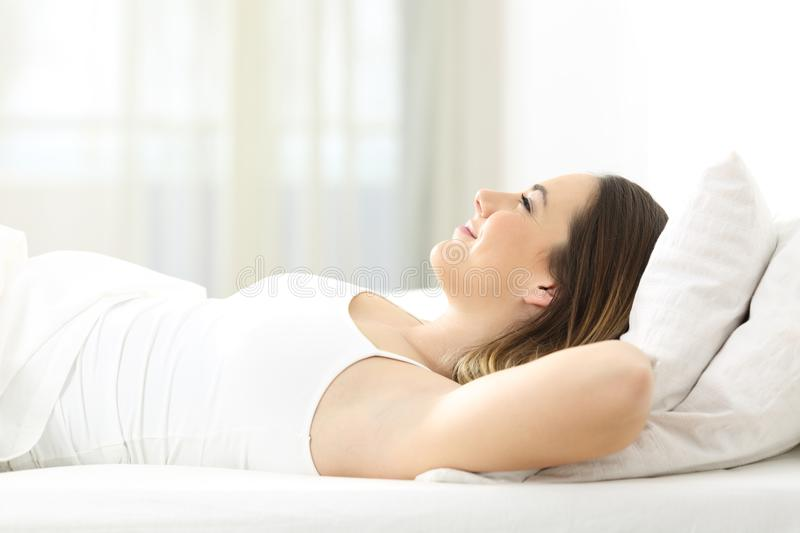 Woman relaxing on the bed at home stock photography