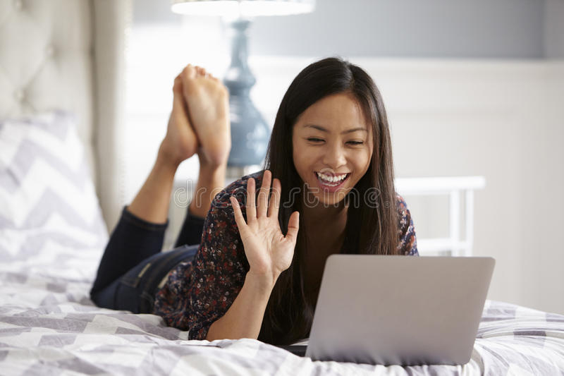Woman Relaxing On Bed Using Laptop Computer For Video Call royalty free stock photography