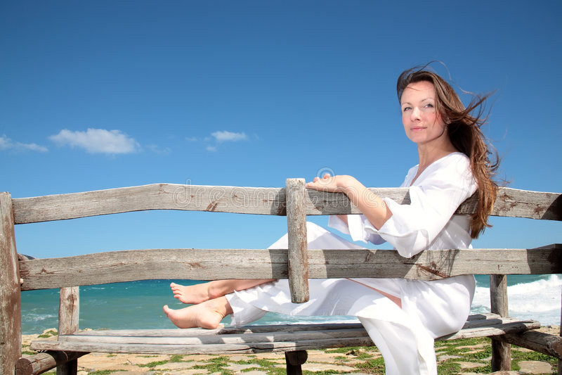 Woman relaxing on the bench. Beautiful young woman relaxing on the bench royalty free stock photography