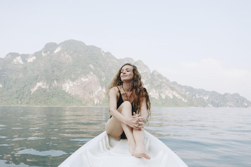 Woman relaxing on a canoe at a lake stock photos