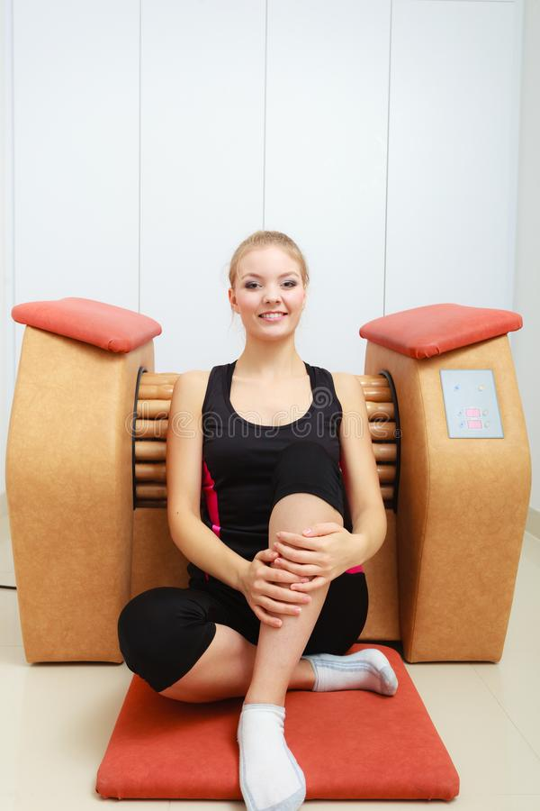 Woman relaxing after cellulite treatment on machine. Skincare, bodycare, wellness concept. Woman relaxing after getting rid of cellulite on big roll machine royalty free stock images