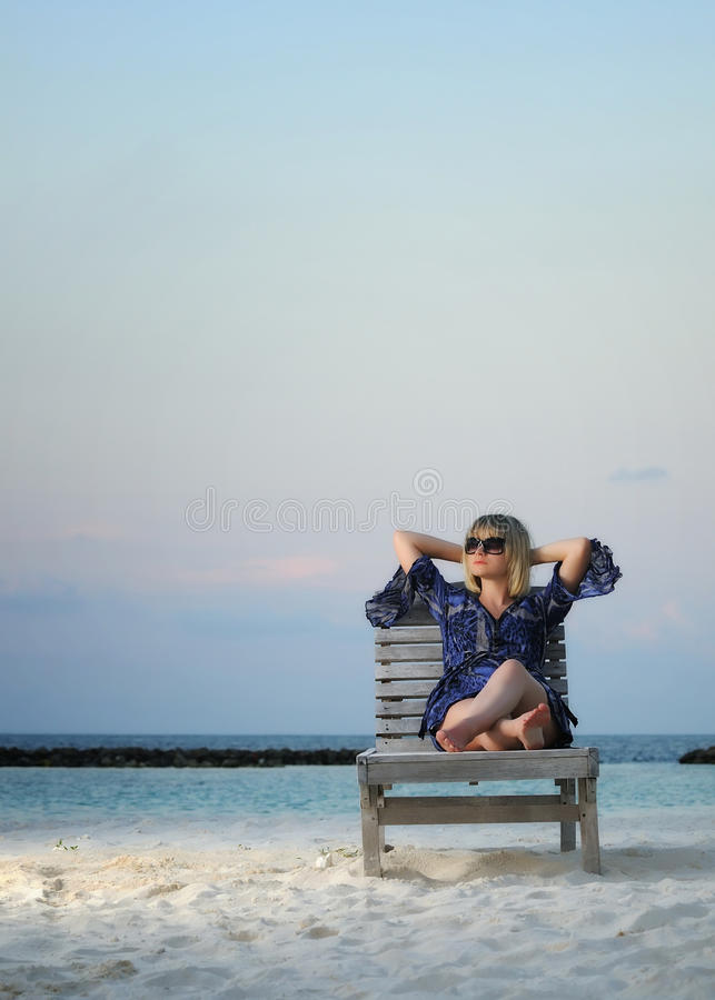 Woman relaxing in a chair. Woman relaxing on the beach in coming twilight. Vertical frame with copy space stock photo
