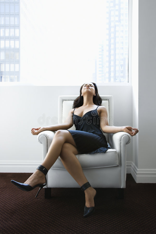 Woman relaxing in chair. Hispanic woman relaxing in armchair with window to city in background royalty free stock image