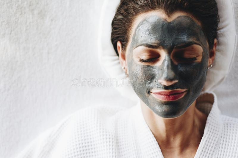 Woman relaxing with a charcoal facial mask royalty free stock images