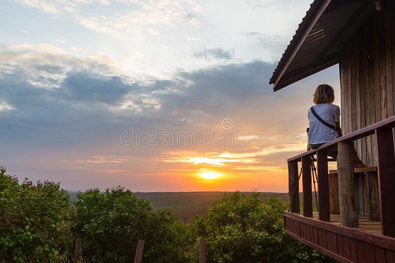 Woman relaxing in the countryside, sitting in balcony wooden cabin, watching dramatic sky at sunset, traveling wanderlust, royalty free stock photography