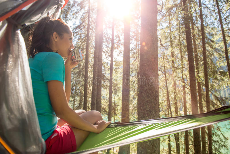Woman relaxing and drinking in hanging tent camping in forest woods during sunny day.Group of friends people summer. Adventure journey in mountain nature stock photos