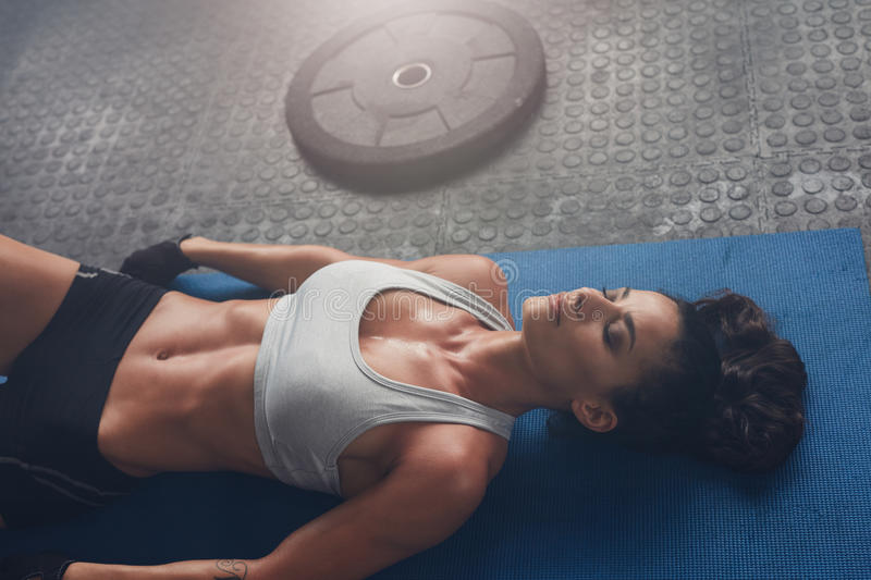 Woman relaxing after exercise session. Top view shot of woman relaxing after exercise session with a heavy weight plate on floor. Young woman lying on exercise stock images