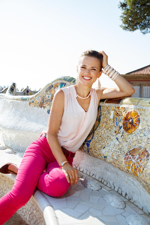 Woman relaxing on the famous trencadis style bench. Get inspired by Park Guell in your next trip to Barcelona, Spain. Smiling young woman relaxing on the famous stock photos