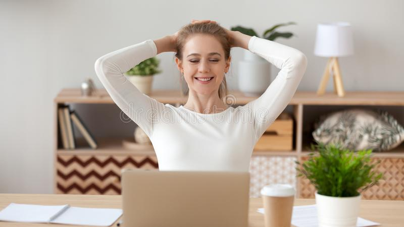 Woman relaxing after finished computer work, looking at screen. Smiling young woman relaxing leaning back with hands behind head after finished computer work royalty free stock photography