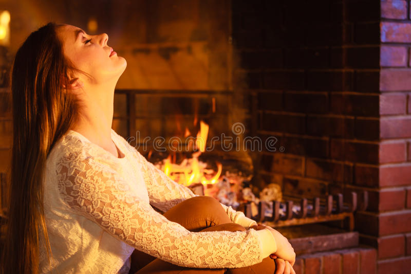 Woman relaxing at fireplace. Winter home. Woman relaxing resting at fireplace. Young girl heating warming up. Winter at home stock image