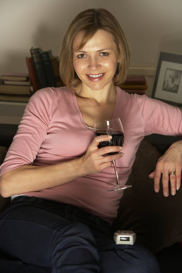 Woman Relaxing With Glass Of Wine Watching TV