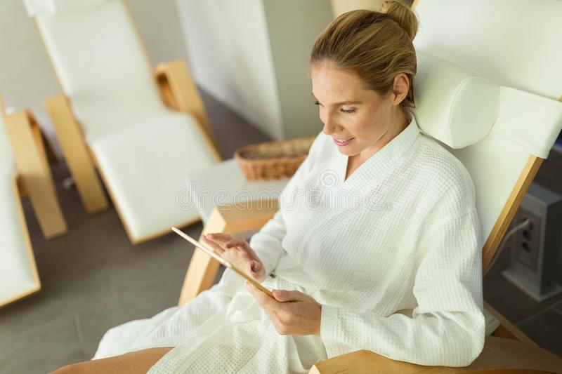 Woman relaxing in gown at spa resort. On massage bed royalty free stock images