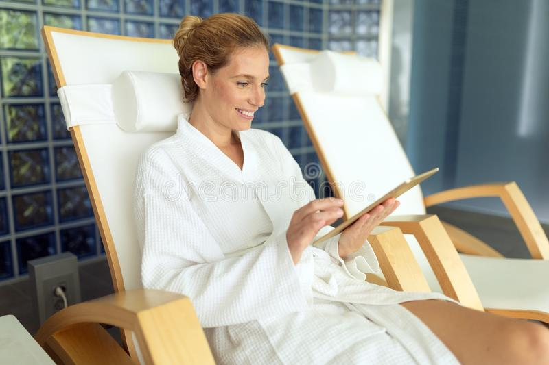 Woman relaxing in gown at spa resort. On massage bed stock photography