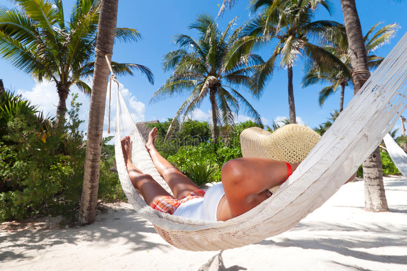 Woman relaxing in the hammock. Between palm trees stock images