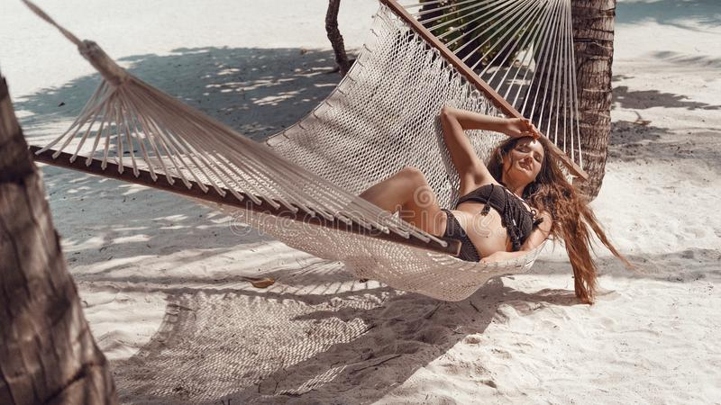 Woman relaxing in the hammock on tropical beach, summer vaction. Free girl chilling on exotic island. Background stock photos