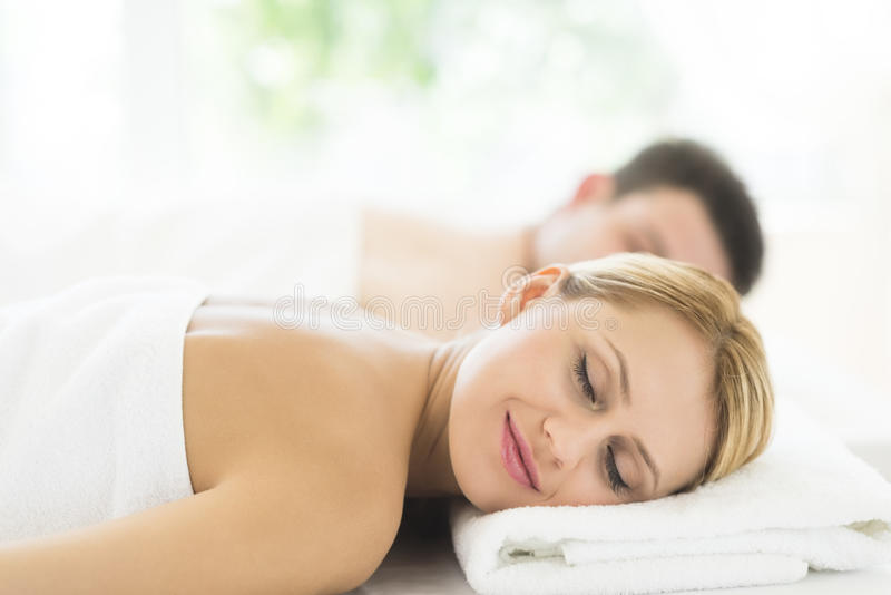 Woman Relaxing At Health Spa. Young women relaxing at health spa with men in background stock photo